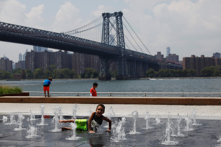 Child cools off from the hot weather at Domino Park in the Williamsburg section of Brooklyn